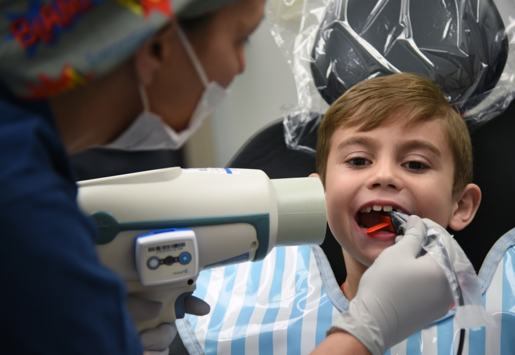 kid at dentist getting x-ray to find cavities
