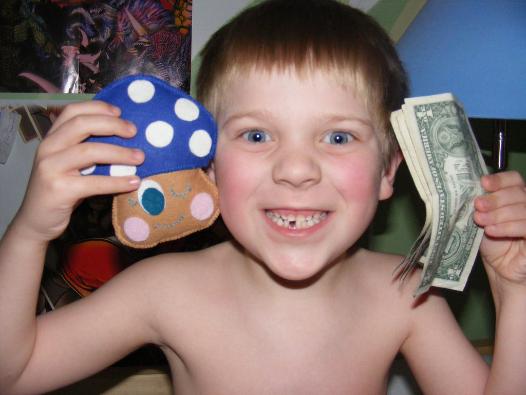 Excited kid with tooth fairy pillow and cash