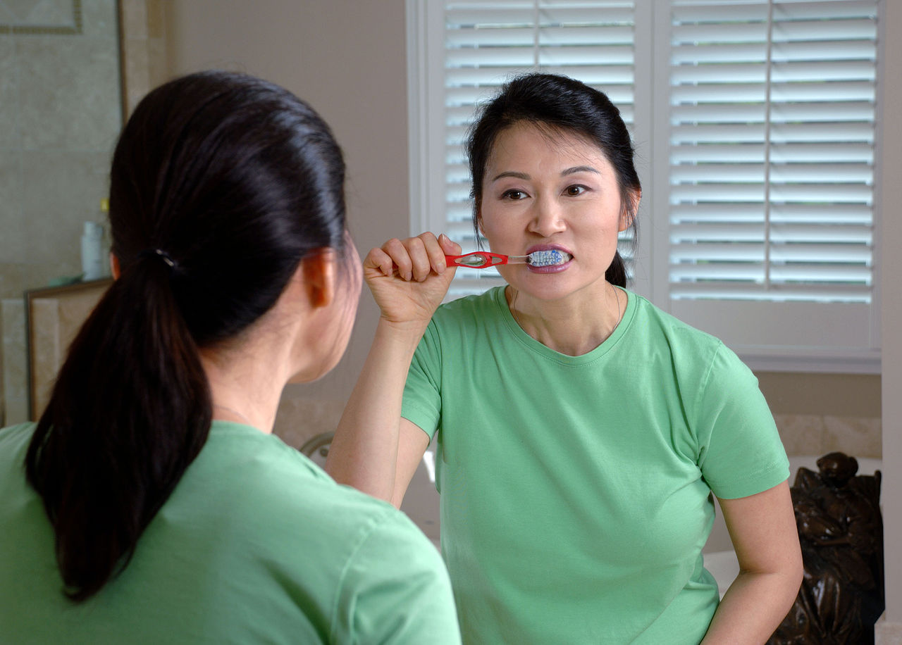 woman brushing teeth in mirror for good oral care
