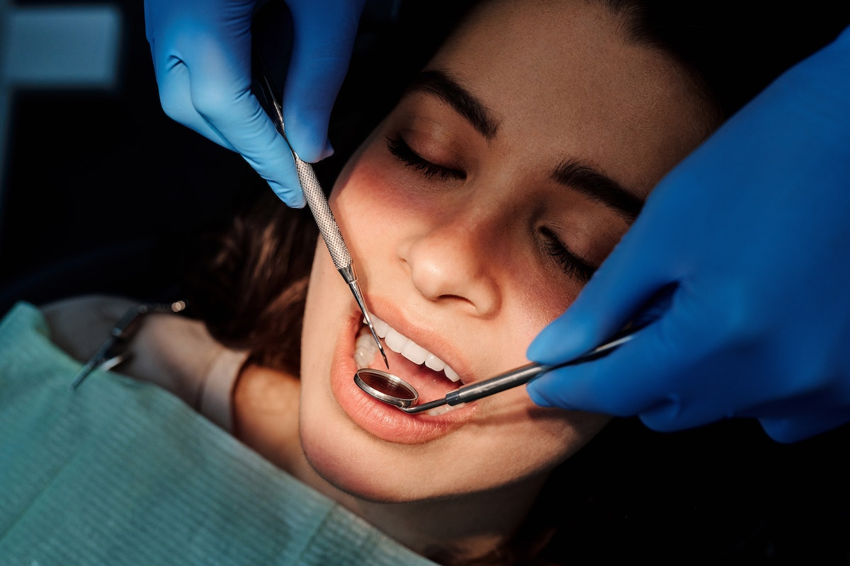 Dentist performing a check-up on a woman with healthy teeth and gums after using mouthwash with braces