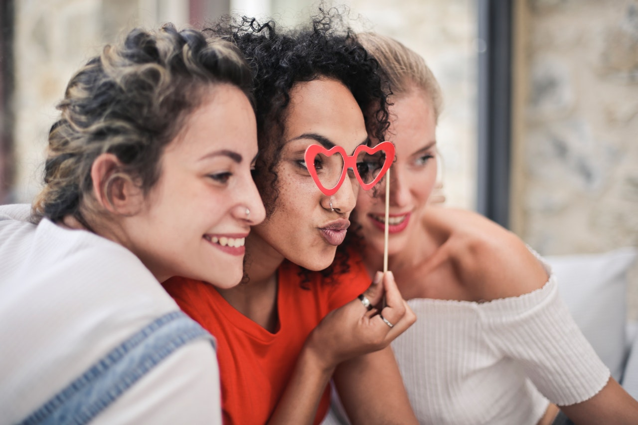 Three women looking through heart glasses