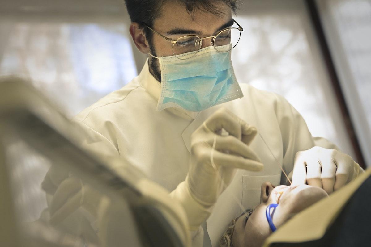 Oral surgeon performing wisdom teeth extraction