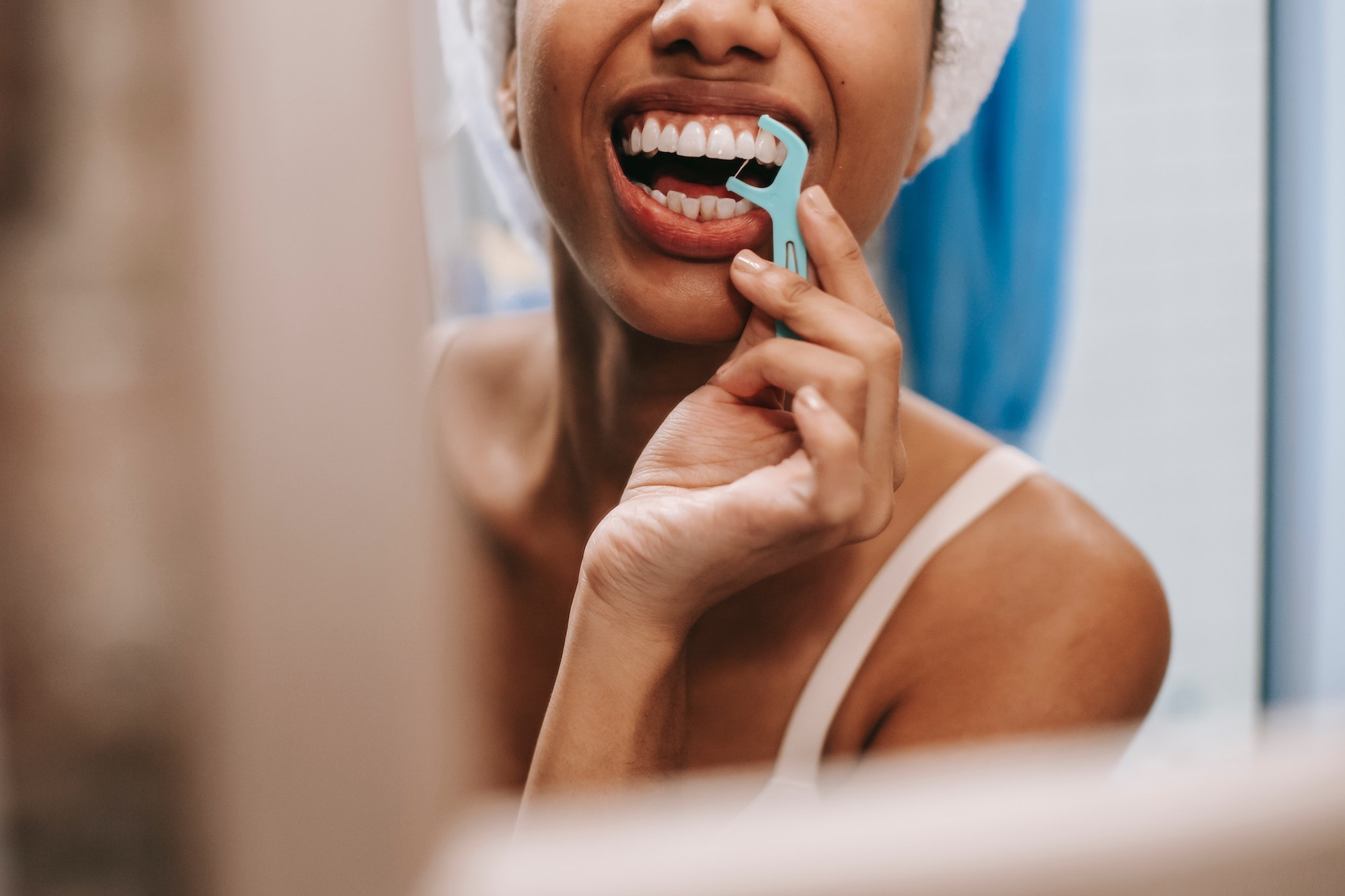 Woman flossing gently to reduce sensitivity after getting a cavity filled