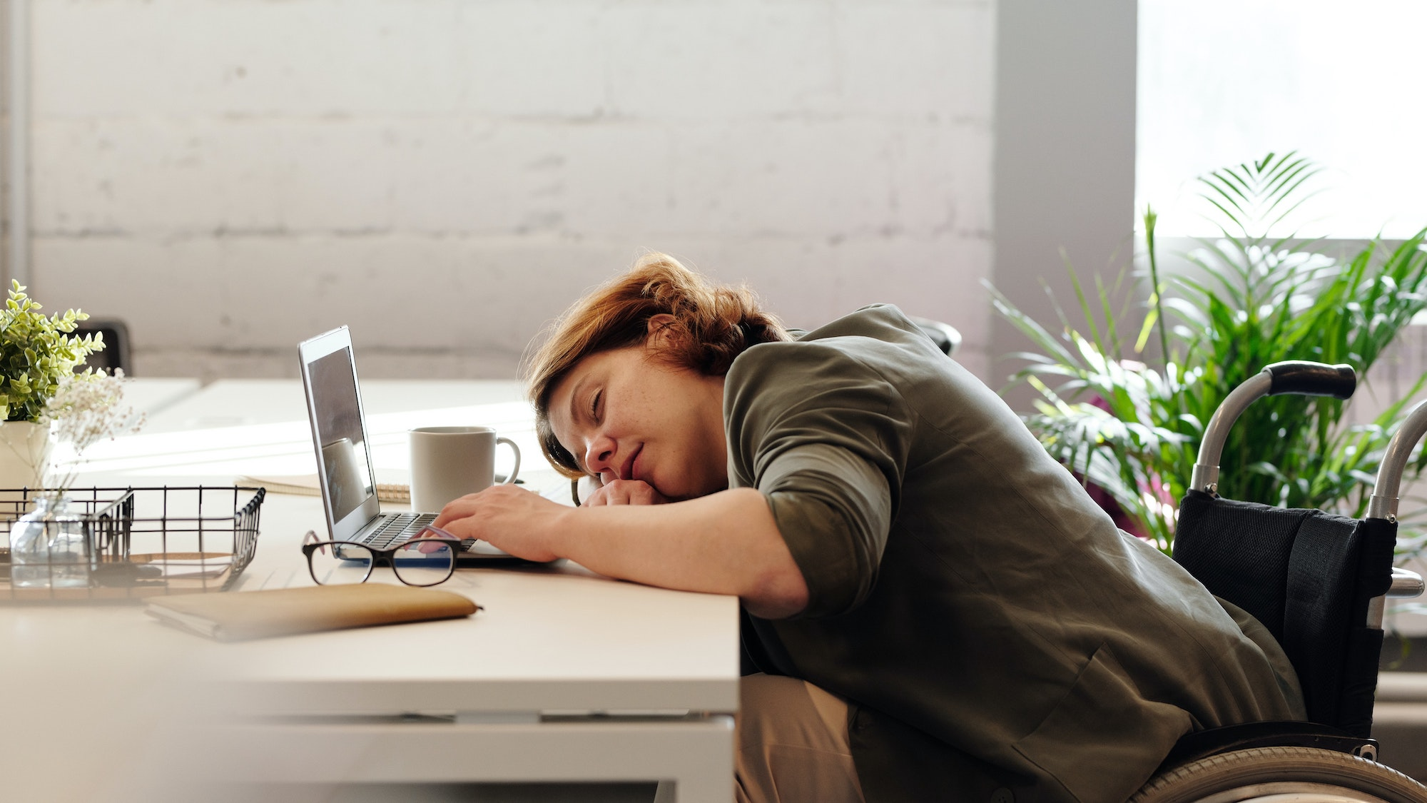 Woman asleep at her laptop after getting bad sleep due to teeth grinding at night