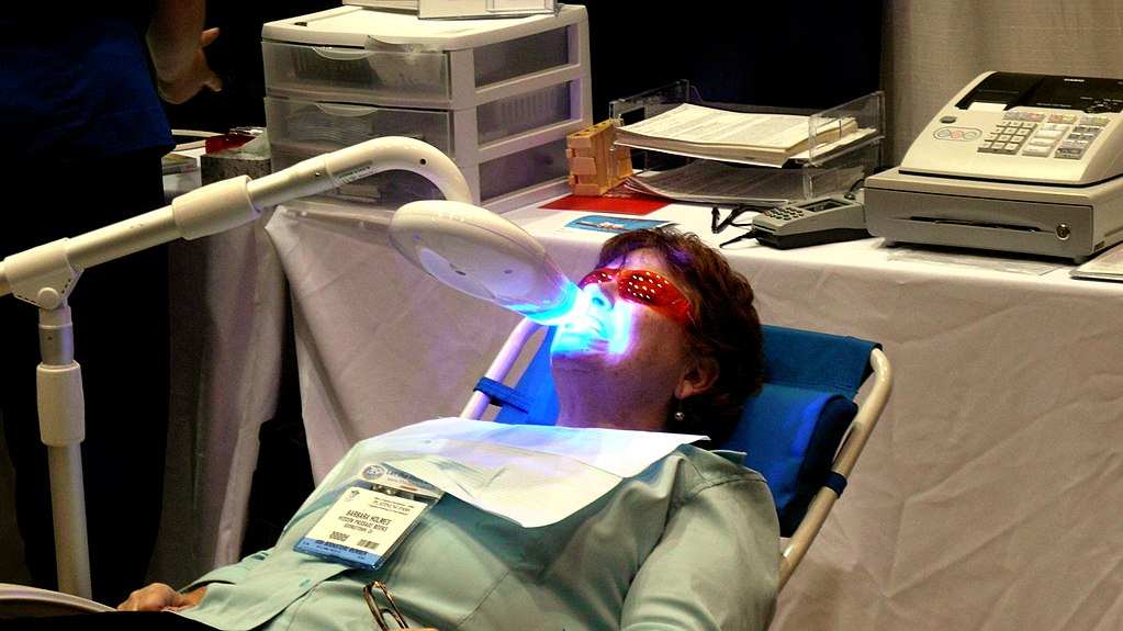 woman in dentist chair receiving zoom teeth whitening treatment